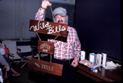 Bill holding Wild Bill's Coffeeshop sign